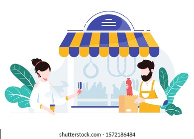 Customer making a purchase at local meat shop. Helpful shopkeeper wearing apron packs fresh sausage and meat in a store.