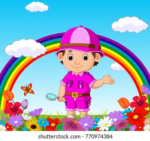 Cute boy holding magnifying glass in a flower garden with rainbow