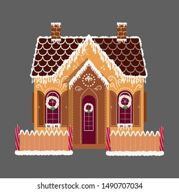 Cute decorative gingerbread house with patterns and candles.
