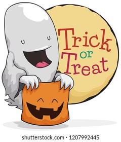 """Cute ghost with a smiling candy basket like a pumpkin ready for the traditional """"trick or treat"""" during Halloween celebration."""