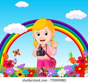 Cute girl in a flower garden with rainbow