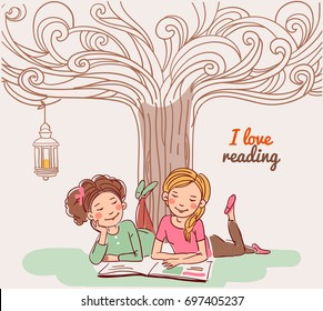 Cute girls reading a book under the tree