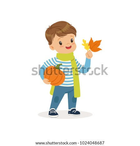 Cute little boy in warm scarf holding pumpkin and colorful maple leaves 026f12c487387