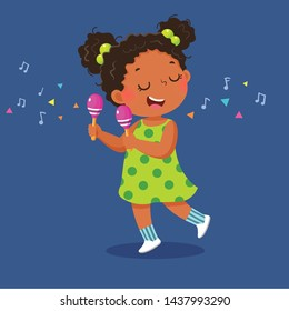 Cute little girl playing the maracas on blue background