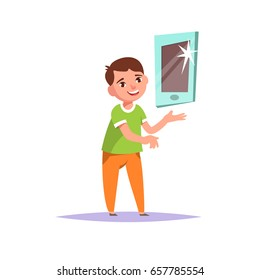 Cute smiling boy standing and showing promotion product on white background. Advertising the new gadget