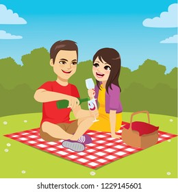 Cute young couple on picnic day enjoying wine sitting on patterned blanket at park with basket