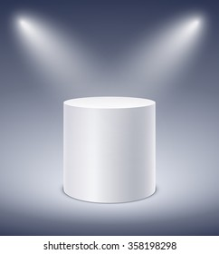 Cylindrical podium in glow of spotlights