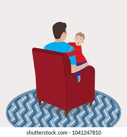 Dad sits in the armchair and holds a son in her arms