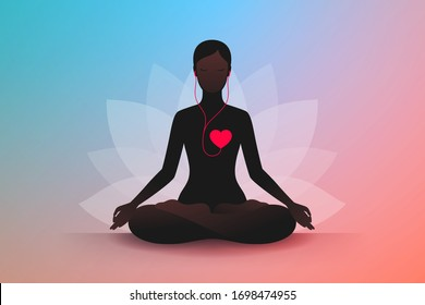 Dark silhouette of slender woman sitting in lotus position, listening music of her heart and meditating. Listen to your heart. Concept of harmony and tranquility in heart and thoughts