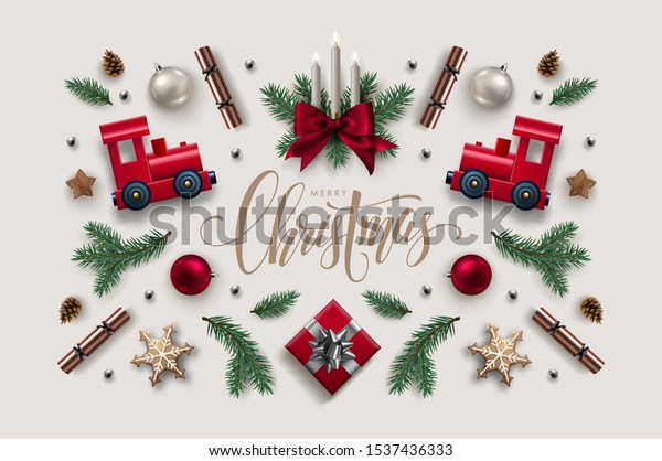 Decorative Frame made of Christmas Ornaments, Pine Branches, Burning Candles and Red Toy Trains Flat lay, top view.