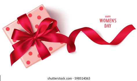 Decorative gift box with red bow and long ribbon. Happy Women's Day text. Top view