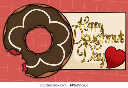 Delicious, homemade half bitten donut over tablecloth with chocolate and vanilla glaze, filled with strawberry marmalade, greeting sign and heart to celebrate Doughnut Day.