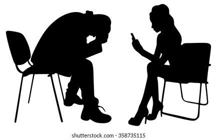 Depressed man sitting with his girlfriend texting on her cell phone