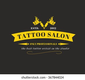 Design of a logo with gold tattoos machines and a ribbon on a black background for a tattoo of salon, studio or the artist. Vector illustration