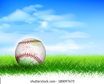 Detailed used baseball on lush grassy field.