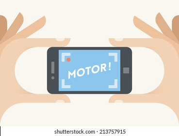 Director taking a video mobile phone camera with Motor! text on screen. Idea - Home video, Movie directors and filmmakers, Hollywood, New video capturing technologies etc.