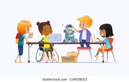 Disabled African American girl in wheelchair and other children standing around desk with laptops and robot and working on school project for programming lesson. Concept of inclusion at school.