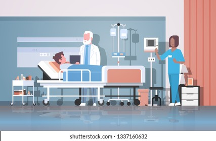 doctor and nurse visiting patient man lying bed with dropper intensive therapy ward healthcare concept hospital room interior modern medical clinic horizontal full length