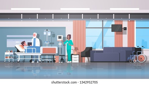 doctor and nurse visiting patient man lying bed with dropper intensive therapy ward healthcare concept hospital room interior modern medical clinic horizontal banner full length