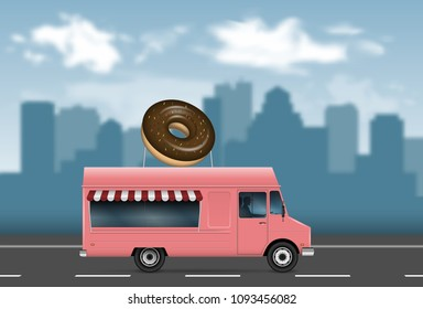 Donut truck on the blurred city background.
