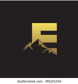 E alphabet mountain negative space letter logo gold black background
