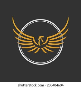 Eagle Logo Icon Design. Stock vector. Eagle Logo Icon Design. Stylized eagle spreads its wings. Golden and silver color on the dark background.