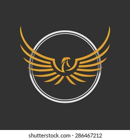 Eagle Logo Icon Design Template. Vector Illustration Eagle Logo Icon Design. Stylized eagle spreads its wings. Golden and silver color on the dark background.