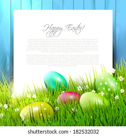 Easter background with colorful eggs in grass and empty paper