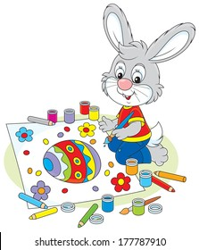 Easter Bunny drawing a colorfully decorated egg and flowers on a big sheet of paper