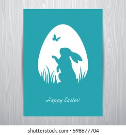 Easter greeting card design with standing rabbit silhouette in an egg shaped white frame. Placed on a grey wooden background.