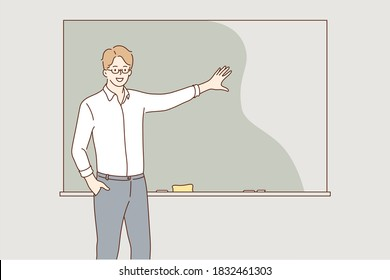 Education, training, explanation, lecture concept. Young hapy smiling man guy student teacher lecturer character explaining material on school lesson near blackboard. Educational process at university