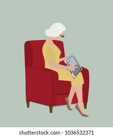The elderly woman sitting on her chair holds a computer tablet