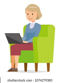 An elderly woman wearing blue clothes is sitting on a sofa and operating a laptop computer