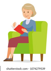 An elderly woman wearing blue clothes is reading on a sofa
