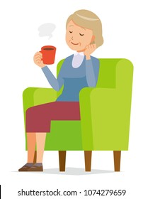 An elderly woman wearing blue clothes is sitting on a sofa and drinking coffee