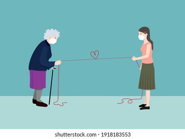 Elderly woman and young woman with protective masks holding a red rope with a heart shaped knot to keeping the social distance in the outbreak. Protecting our beloved ones concept.