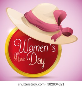 Elegant lady hat with pink ribbon and bow on top of glossy golden button with Women's Day message inside it.