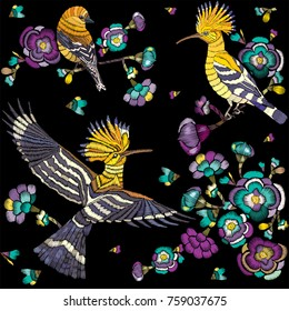 Embroidered birds and flowers on a black background. Embroidered seamless floral pattern of the traditional Japanese style.  Can be used for the design of clothing, textiles and manufacturing