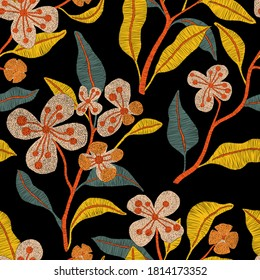 Embroidered seamless pattern. Isolated branches of flowers on a black background. Bohemian print for textiles and home decor. Vector illustration.