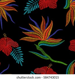 Embroidery Bird of Paradise flowers, tropical Strelitzia, hibiscus seamless pattern. Vector fashion ornamental floral print on black background for fabric traditional folk decoration