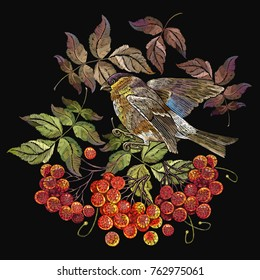 Embroidery bird sitting on mountain ash branch. Fashionable template for design of clothes. Titmouse on a branch of mountain ash berry