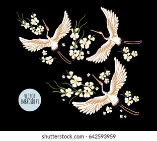 Embroidery colorful floral pattern with flowers, japanese white crane. Vector traditional folk fashion ornament on black background.