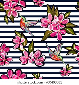 Embroidery colorful floral pattern with  japanese flowers, sakura, hummingbirds. Vector traditional folk fashion ornament on black background.