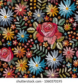 Embroidery seamless pattern with colorful flowers, leaves and berries on black background. Fashion design for fabric, textile, wrapping paper. Fancywork print. Vector illustration.