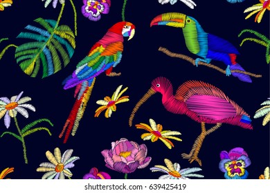 Exotic birds paradise. Seamless vector pattern with embroidered parrot, toucan and ibis on dark blue background. Beach textile collection.