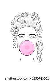 The face of a girl in a wig inflates a bubble of chewing gum.