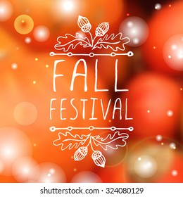 Fall festival. Hand-sketched typographic element with acorns on blurred background.