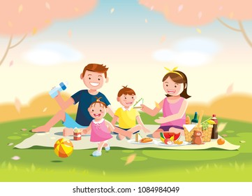 Family enjoying picnic. They are sitting on the grass in a park, the basket with meal and toys for the kids. Blurred background.