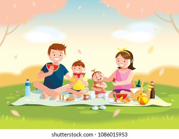 Family enjoying picnic. They are sitting and eating watermelon on the grass in a park, the basket with meal and toys for the kids. Blurred background.