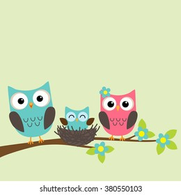 Family of owls with newborn owlet sitting on the branch of blooming tree